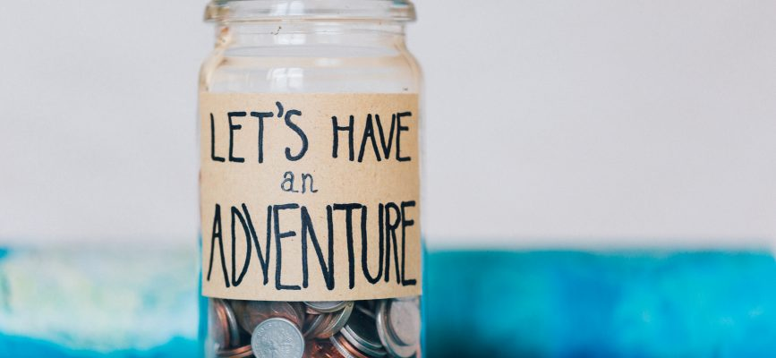 "Mixed denomination and currency coins in a glass jar with handwritten label ""Let's Have An Adventure"""